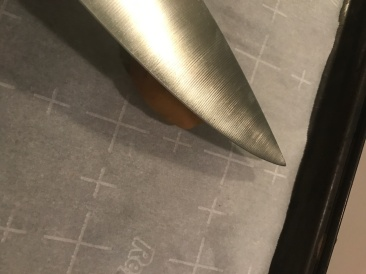 Squishing the balls with the side of a large knife. Do not cut yourself.